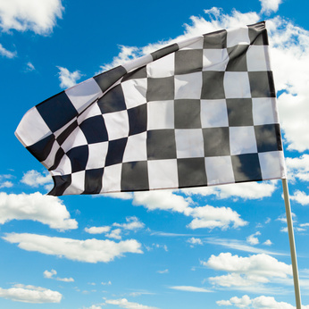 Checkered flag against the blue sky with clouds